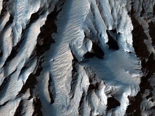 El Tithonium Chasma (parte de Valles Marineris de Marte) está cortado con líneas diagonales de sedimento que podrían indicar ciclos antiguos de congelación y fusión, según LiveScience.